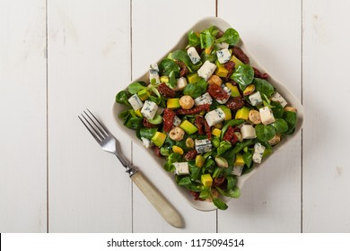 Italian salad with avocado, gorgonzola cheese, pistachio nuts, sun-dried tomatoes and croutons. Top view. White woodem background.