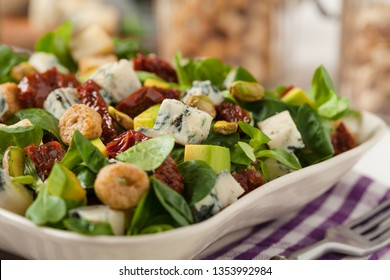 Italian salad with avocado, gorgonzola cheese, pistachio nuts, sun-dried tomatoes and croutons. Front view. White woodem background.