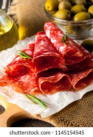 Italian salami with olives and spices on wooden background