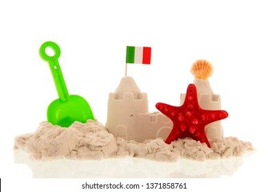 Italian sandcastle with red toys and flags isolated over white background