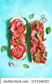 Italian sandwith with prosciutto crudo, mozzarella cheese, salame and basil on a blue slate, stone or concrete background.Top view with copy space.