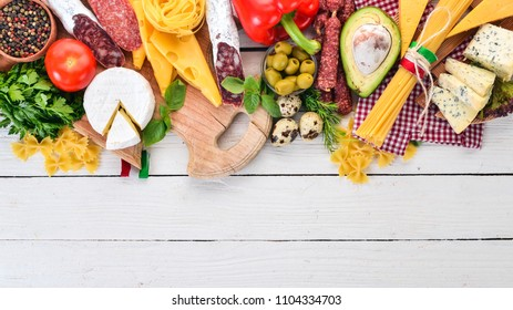 Italian sausage, cheese and vegetables. On a white wooden background. Top view. Copy space.