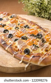 Italian Sausage Pizza on brown base and wooden table