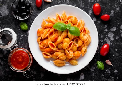 Italian shell pasta with tomato sauce, olives and Basil, classic food