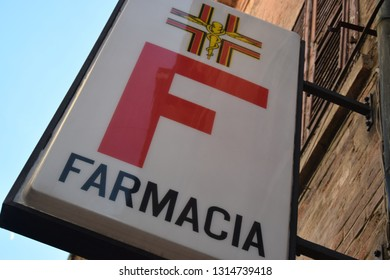 Italian sign of a pharmacy, farmacia, red and white in a old city center, medical
