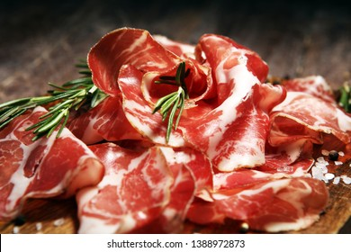 Italian sliced cured coppa with spices. Raw ham. Crudo or jamon on wood