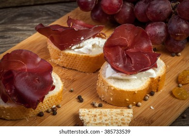 Italian sliced prosciutto on bread and grapes in the back on wooden table in studio photo
