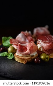 Italian smoked prosciutto canapes with green and black olives and basil herb garnish shot against a black background with generous accommodation for copy space.