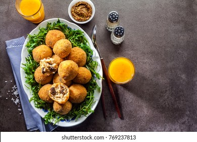 Italian snack. Fried balls from rice Arancini with mushrooms, cheese with mustard sauce and a salad of rucola on a gray stone table with freshly squeezed orange juice. fast healthy hearty meal