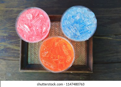 Italian soda in plastic cup on wood tray