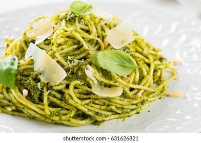 Italian spaghetti with homemade basil pesto with parmigiano and basil leaves, healthy food, on white background