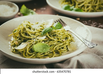 Italian spaghetti with homemade basil pesto with parmigiano, healthy food, on dark wooden background, top view