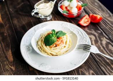Italian spaghetti with meat decorated with mint leaves and a salad with tomatoes and mozzarella