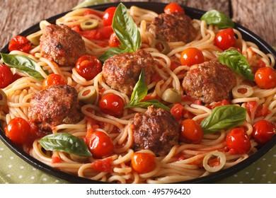 Italian spaghetti with meatballs, olives, basil and tomato sauce closeup on a plate. horizontal