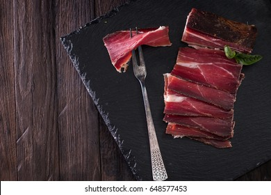 italian Speck, delicious ham on vintage background