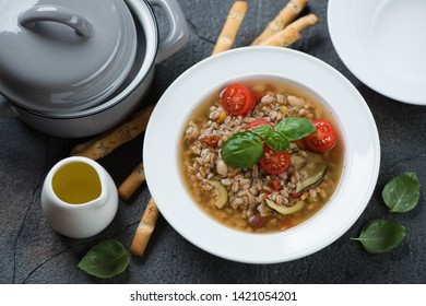 Italian spelt and minestrone soup, high angle view over grey stone background, horizontal shot