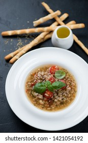 Italian spelt and minestrone soup with salted breadsticks and olive oil, vertical shot over black stone background