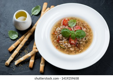 Italian spelt and minestrone soup served with grissini over black stone background, studio shot