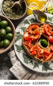 Italian starter freselle. Classical fresella tomato,  olives and basil with oregano and olive oil. Dried bread called freselle on white plate. Italian food. Healthy vegetarian food.