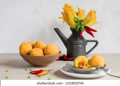 Italian still life with arancini and flowers of pumpkins. Arancini - italian rice balls which are coated with bread crumbs and then deep fried, filled with ragu (meat and tomato sauce) and peas.