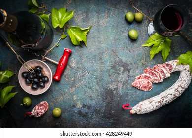 Italian still life with salami, red wine, olives and grape leaves on dark rustic background, top view, place for text. Italian food background