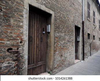 Italian street with wooden doors and brick wall. You can see old mail boxes.