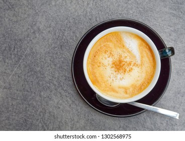 Italian style cappuccino coffee black cup on grey granite background, top view