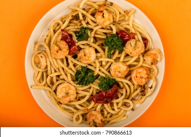 Italian Style Meal of King Prawn Bucatini Against An Orange Background