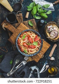Italian style pasta dinner. Spaghetti with tomato and basil in plate on wooden board and ingredients for cooking pasta over dark blue wooden background, top view