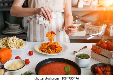Italian style pasta dinner. Pasta with tomato and basil in plate on the wooden rustic table and ingredients for cooking. Chef hands preparing delicious pasta with tomato sous. Homemade food.