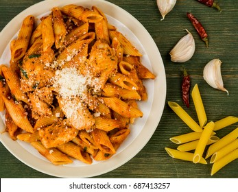 Italian Style Spicy Chicken Penne Pasta Arrabbiata Against a Green Wooden Background