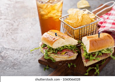 Italian sub sandwich with salami, ham and chips with copy space