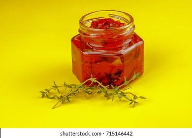 Italian sun dried tomatoes in glass jars on yellow background