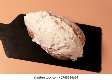 """Italian sweets """"Maritozzo"""". Sweet and fresh whipped cream sandwiched between brioches."""