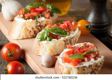Italian tomato and cheese bruschetta. Tapas, antipasti with chopped vegetables, herbs and oil on grilled ciabatta and baguette bread.