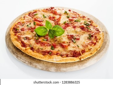 Italian tomato Margherita pizza with fresh leaf of basil, served on round wooden cutting board, viewed in close-up from high angle, isolated on white background