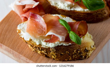 Italian tomato, prosciutto, jamon, ham and cheese bruschetta. Tapas, antipasti with chopped vegetables, herbs and oil on grilled ciabatta and baguette bread.