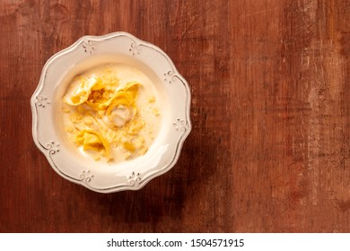 Italian tortellini in a cream sauce with grated Parmesan cheese, shot from above on a dark rustic wooden background with copyspace