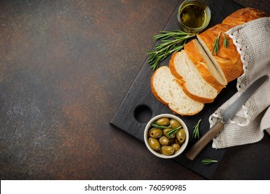 Italian traditional Ciabatta bread with olives, olive oil, pepper and rosemary on a dark stone or concrete background. Selective focus.Top view. Copy space.