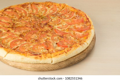 Italian traditional classical pizza Margherita. Pizza Margarita on round board on wooden table background