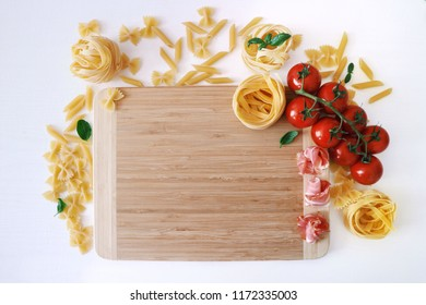 Italian traditional food, pasta, appetizers. Prosciutto, cherry tomatoes, fresh basil leaves on a wooden board on a white background. Various pasta. Space for text.