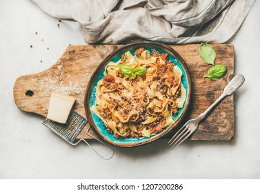 Italian traditional pasta dinner. Flat-lay of tagliatelle bolognese with minced meat, tomato sauce and parmesan cheese over rustic wooden board on white marble table, top view, horizontal composition