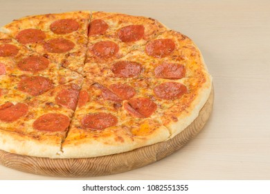 Italian traditional pepperoni pizza on round board on wooden table background