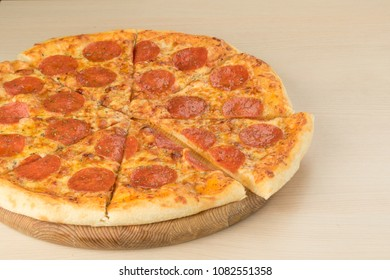 Italian traditional pepperoni pizza on round board with slice as
