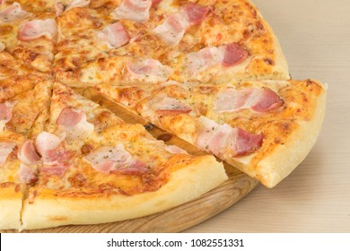 Italian traditional pizza with bacon ham on round board on wooden table background. Closeup of slice aside
