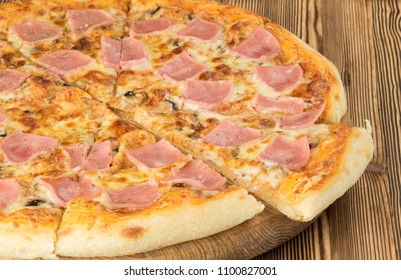 Italian traditional pizza with bacon ham on round board with slice aside on wooden table background