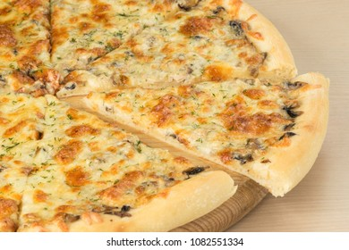 Italian traditional pizza with mozzarella cheese on round board on wooden table background. Closeup of slice aside