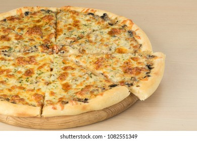 Italian traditional pizza with mozzarella cheese on round board with slice aside on wooden table background