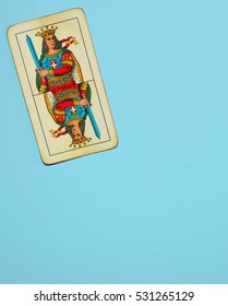 Italian traditional playing card showing a king with a sword, hanging on a sky blue wall.