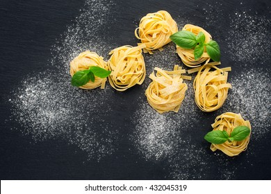Italian traditional raw pasta and basil on the black stone background, top view